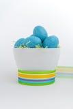 Blauwe gespikkelde eieren in Pasen-gras met trillend lint Stock Foto's