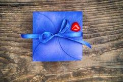 Blauwe giftdoos met een lintlint en een hart op een houten achtergrond stock afbeeldingen