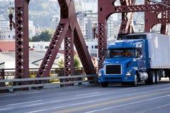 Blauwe grote de installatie semi vrachtwagen die van de dagcabine commerciële lading binnen vervoeren stock afbeelding