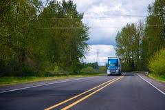 Blauwe grote installatie semi vrachtwagen op groene weg met bomen Stock Fotografie