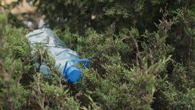 Blauwe grote plastic fles die op de grond in boom in een Weggegooid parkbos liggen - gerecycleerd niet - Afval en verontreiniging stock videobeelden