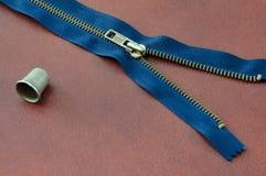 Blauwe half opengeritste ritssluiting en vingerhoedje, bruine leerachtergrond Stock Afbeeldingen