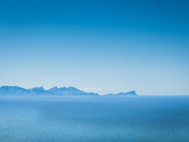 Blauwe hemel, blauwe oceaan en in de afstand, blauwe bergen Stock Afbeeldingen