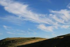 Blauwe hemel boven de schaduwrijke heuvel royalty-vrije stock foto