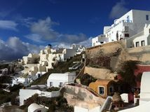 Blauwe hemel boven Oia en de vergoelijkte huizen die de helling koesteren Royalty-vrije Stock Afbeelding