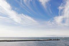 Blauwe hemel, de Oostzee en een kleine vuurtoren stock fotografie