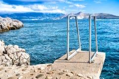 Blauwe hemel en duidelijk water, overzeese horizon en rotsen op eilandbehang stock fotografie