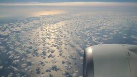 Blauwe hemel en witte pluizige wolkenmening van hierboven door het venster van het vliegtuig bij zonsopgang stock videobeelden