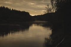 blauwe hemel en wolken die in kalm water van rivier Gauja in Letland in de herfst nadenken - uitstekende retro ziet eruit stock foto's