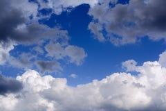 Blauwe hemel met onweerswolken De regenwolken worden verlicht door r Royalty-vrije Stock Afbeelding