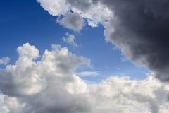 Blauwe hemel met onweerswolken De regenwolken worden verlicht door r Stock Afbeelding