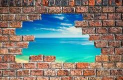 Blauwe hemel met overzees door het gat in de bakstenen muur Stock Afbeelding