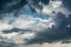 Blauwe hemel met witte wolken en krullende donkere regenwolken De achtergrond van de hemel Royalty-vrije Stock Afbeelding