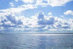 Blauwe hemel met witte wolken over groot meer royalty-vrije stock afbeeldingen