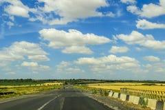 Blauwe hemel met witte wolken over weg Royalty-vrije Stock Afbeelding