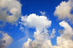 Blauwe hemel met wolken en een regenboog Stock Foto's
