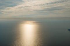 Blauwe hemel met wolken en vliegtuigslepen over de Zwarte Zee De zontrein op de overzeese oppervlakte en een boot met boot sleept Royalty-vrije Stock Afbeelding