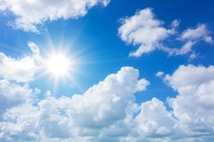 Blauwe hemel met wolken en zonbezinning De zon glanst binnen helder royalty-vrije stock afbeelding