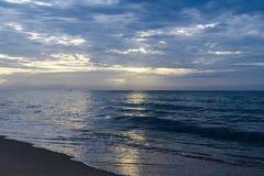 Blauwe hemel met wolken oranje bezinningen over het water en de kustlijn op de horizon stock fotografie