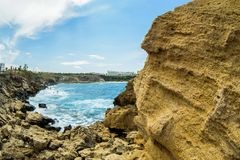 Blauwe hemel met wolken over overzeese oppervlakte Rotsachtige kustmening in zonnige dag Royalty-vrije Stock Foto