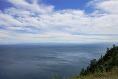 Blauwe hemel met wolken over overzeese oppervlakte Rotsachtige kustmening in zonnige dag Stock Foto