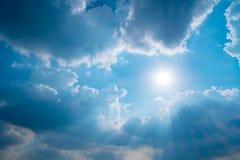 Blauwe hemel met zon en wolken stock foto's