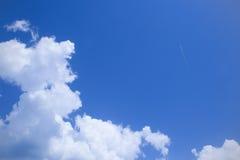Blauwe hemel, wit wolken en spoor van vliegtuig Royalty-vrije Stock Afbeeldingen
