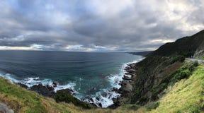 Blauwe hemel, witte branding, rotsachtige kust, witte wolken stock foto's