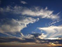 Blauwe hemelachtergrond met kleurrijke dramatische kleurrijke wolken en zonlicht stock foto
