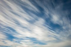 Blauwe hemelachtergrond met uiterst kleine stratus cirrus gestreepte wolken Ophelderingsdag en Goed winderig weer stock afbeelding