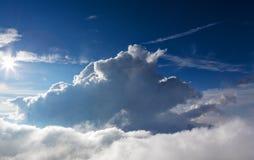 Blauwe hemelachtergrond met witte wolken met zon in kader Stock Foto's
