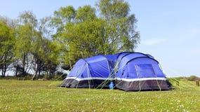 Blauwe het kamperen tent op een gebied van het de lenteland stock afbeeldingen