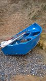 Blauwe het roeien boot op strand Stock Afbeeldingen