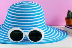 Blauwe hoed en de witte achtergrond van de zonnebril roze muur stock afbeeldingen