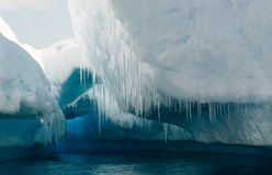 Blauwe hol en ijskegels in doorstane ijsberg, Antarctisch Schiereiland royalty-vrije stock foto