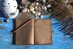 Blauwe houten achtergrond met zand en shells, antiek notitieboekje  Royalty-vrije Stock Afbeeldingen
