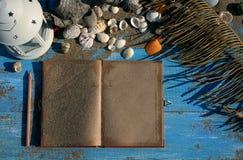 Blauwe houten achtergrond met zand en shells, antiek notitieboekje  Royalty-vrije Stock Fotografie