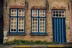 Blauwe houten deur en vensters op de bakstenen muur van huis in Brugge, België royalty-vrije stock fotografie