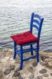 Blauwe houten stoel met rood kussen Stock Foto's