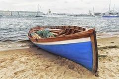 Blauwe houten varende boot met roeispanen bij de banken van rivier Stock Fotografie