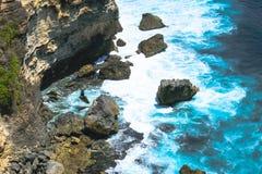 Blauwe Indische Oceaan die de klip en het strand met reusachtige rotsen in Bali, Indonesië wassen stock foto's