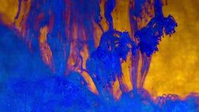 Blauwe inkt met fonkelingen in water op goud Schitter verf die creërend abstracte wolkenvormingen reageren Glanzende achtergrond stock video
