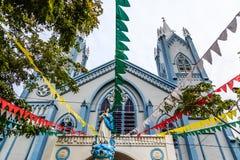 Blauwe Katholieke die kerk met vlaggen en het standbeeld van Heilige wordt verfraaid Mary stock fotografie