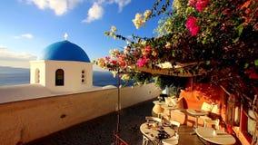 Blauwe kerkkoepel met wind het spelen met kleurrijke bloemstruik op een terras van traditionele cafetaria in het typische Grieks stock video
