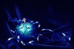 Blauwe Kerstmisbal op een donkerblauw fluweel Stock Afbeeldingen