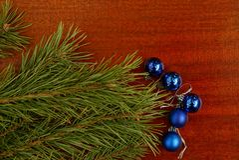 Blauwe Kerstmisballen en groene naaldtakken op een rode lijst Stock Fotografie