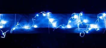 Blauwe Kerstmisslinger op een houten bar Stock Foto