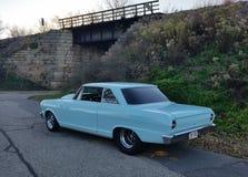 Blauwe klassieke die auto door brug op dalingsdag wordt geparkeerd Stock Foto