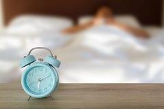 Blauwe klassieke wekker op wit uitstekend houten bureau op vage mensenslaap op de witte achtergrond van het beddegoedblad Royalty-vrije Stock Foto's