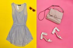 Blauwe kleding, roze handtas, witte schoenen en roze-gekleurde glazen Heldere roze en gele achtergrond Royalty-vrije Stock Fotografie